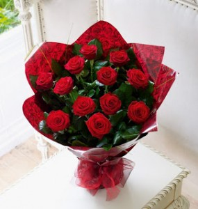 12 Red Roses Wrapped in pointless cellophane and tied with a red silk ribbon