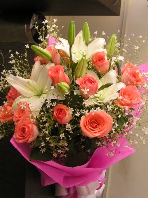 12 Orange Roses with 3 Lilies Bunch wrapped in paper packing